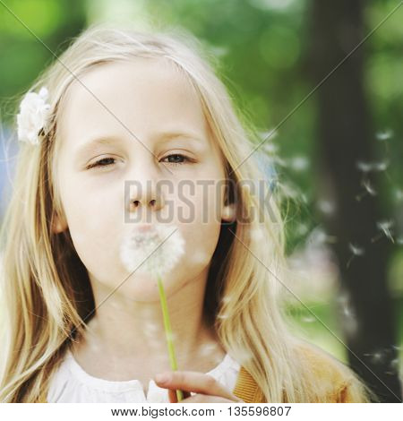 Cute child and dandelion on greenery background