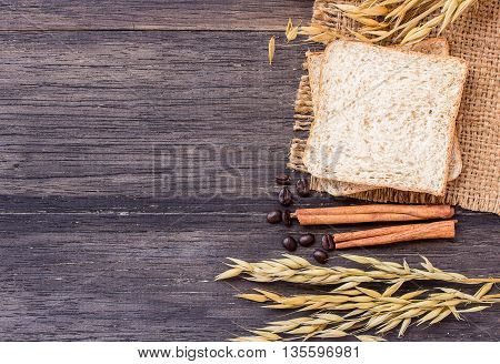 Ears of wheat and slice of bread on a dark wooden table background