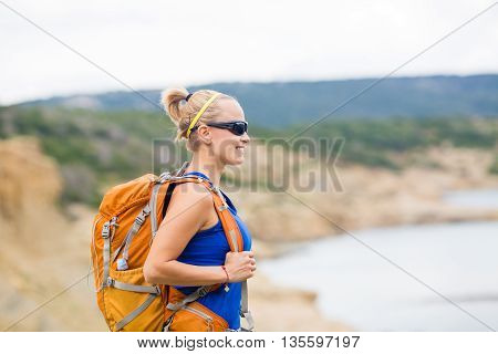 Woman hiking on trail with backpack at seaside on island. Recreation and healthy lifestyle outdoors in summer mountains. Trekking and activity concept in beautiful inspirational landscape.