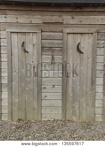 Two old outhouse doors side-by-side in a small town.