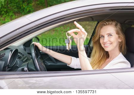 Young woman showing key sitting in car