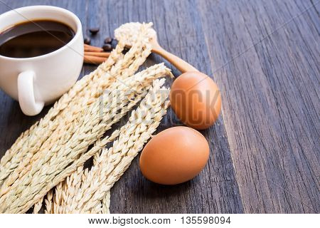 Ears of wheat and coffee with egg on a dark wooden table background.copy space