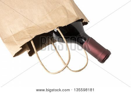 A bottle of red wine in a paper bag overhead view perhaps being given as a gift or bought at a liquor store isolated on white.
