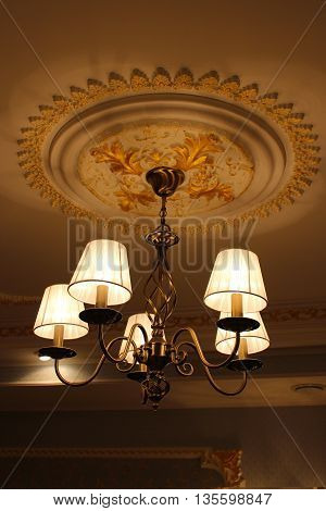Beautiful chandelier under the ceiling with romantic standard lamps