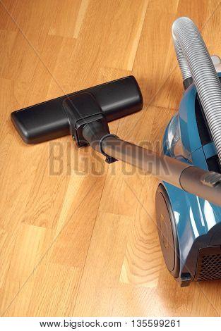 Blue vacuum cleaner on a oak parquet