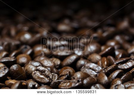 coffee backdrop dark brown roasted beans close up with details in the foreground blurred in the background for copy space selected focus very narrow depth of field