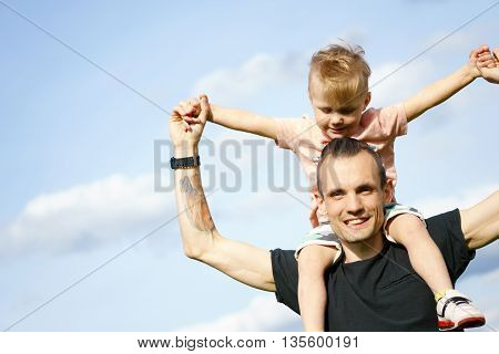 Happy son on the shoulders of his father