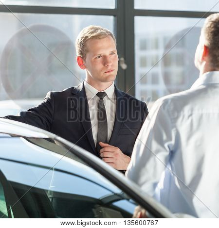 Car agent talking with customer about auto