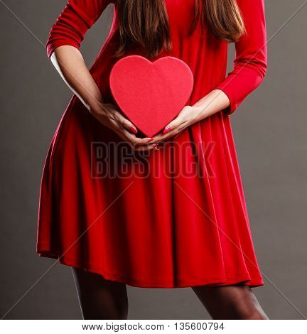 Valentines day love romance concept. Woman in red dress holding heart shaped gift box in hands dark gray background
