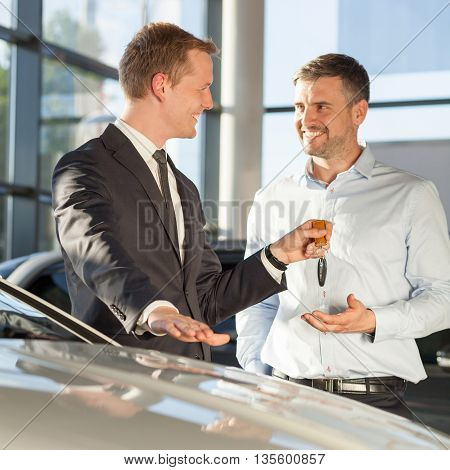 Car dealer giving client keys to his new auto