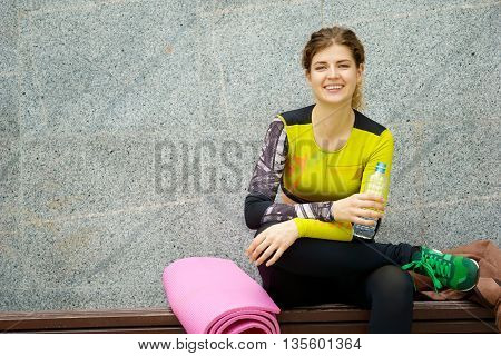 Woman sitting nearly exercise mat, holding plastic bottle of water and resting after workout