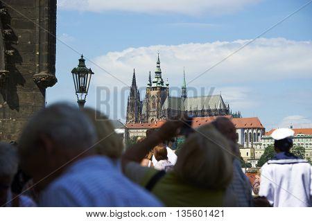 PRAGUE, CZECH REPUBLIC - SUMMER 2014 : Pedestrians and vendors (tourists) walking on the Charles Bridge, Vltava river, Prague the capital city of Czech Republic