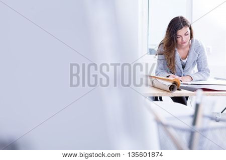 Woman is focused working on a drawing board