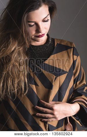 Pensive woman in fashionable outfit is looking down