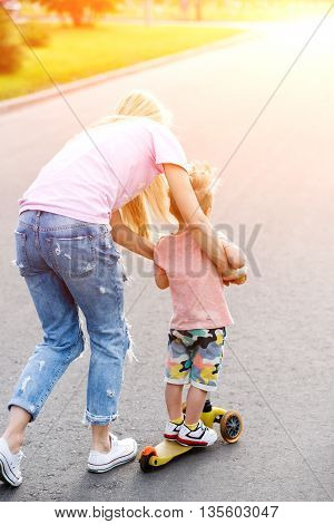 Beautiful girl teaches his son to ride a scooter. lens flare effect