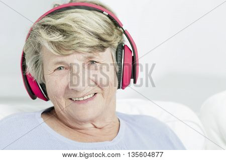 Portrait of a happy senior woman with pink headphones light background