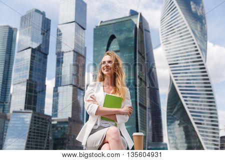 Young pretty woman sitting aganst office buildings with green notebook or diary.