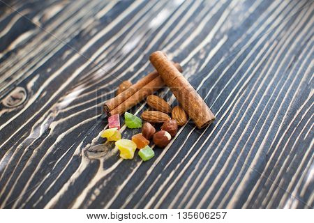 Nuts, candied fruits, cinnamon lie on a textured board