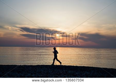 Silhouette of tall sport active man running and exercising on beach at busch below sunset