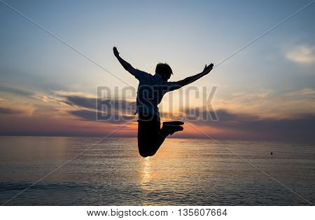 Silhouette man is jumping at the beach on twilight beach background vacation