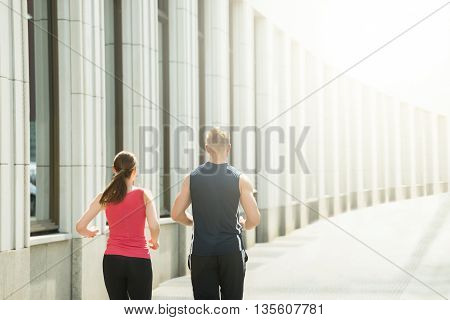 Rear View Of Young Couple Running Together
