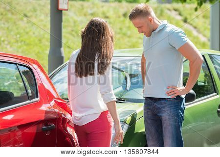Unhappy Young Couple Standing On Street Looking At Broken Down Car