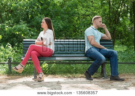 Displeased Young Couple Sitting On Bench In Park