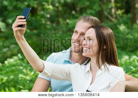 Young Happy Couple Taking Picture With Their Smartphone In Park