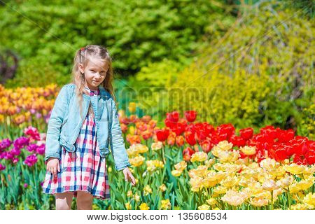 Little beautiful girl in lush tulips garden at warm spring day