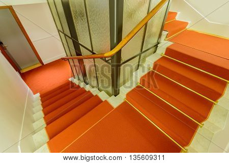 Staircase in red. Abstract fragment of the architecture of modern lobby, hallway of the luxury hotel, shopping mall, business center in Lucerne, Switzerland. Interior design.