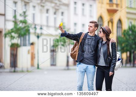 Happy couple dating taking selfie photo with smartphone camera in Europe. Young couple on european vacation holiday. Image from Czech Republic, Prague