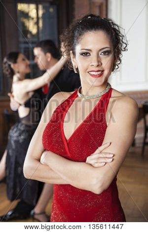 Woman With Arms Crossed Standing While Dancers Doing Tango