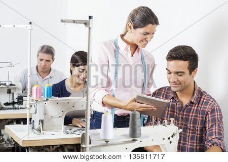 Tailors Using Digital Tablet At Workbench