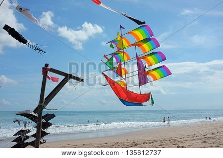 BALI INDONESIA - JUNE 23: A kite in the shape of a sailing ship displays the LGBT flag's rainbow colors on June 23 2016 on a windy sunny Kuta Beach in Bali Indonesia.