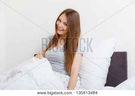 Mornings chilling people concept. Attractive woman in the bed. Beautiful young lady has cosy pyjamas and long hair.