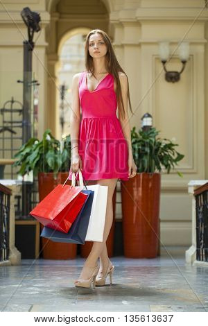 Young beautiful brunette woman with some shopping bags in the mall
