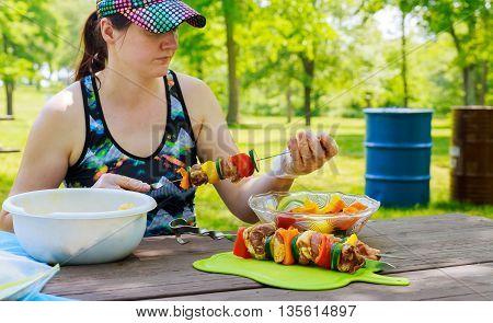 Young happy woman eating chicken shish kebab,