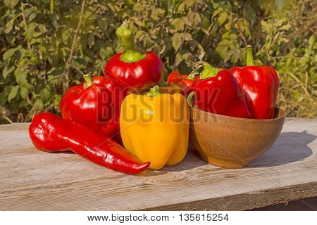 Red and yellow pepper on a wooden background. Different colored peppers on a wood