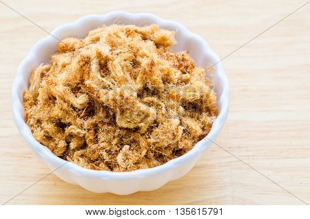 Dried shredded pork chinese food in white cup on wooden background.