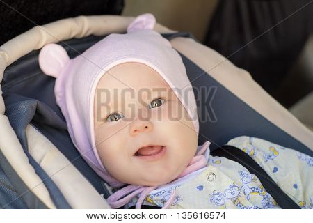 little newborn baby girl rests in the car seat in car