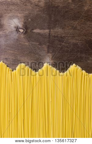 Raw spaghetti noodles on a wooden background
