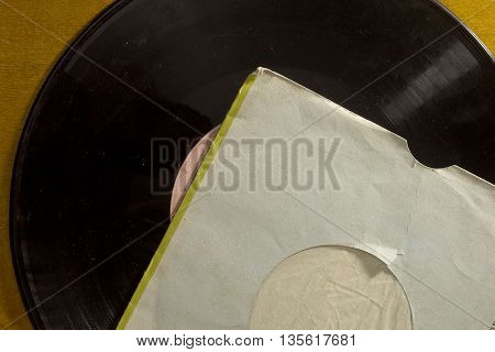 Vintage gramophone vinyl record in an envelope on wooden backgro