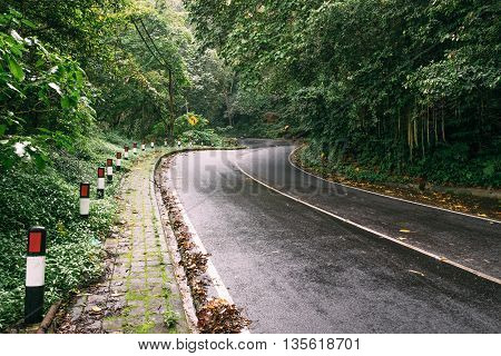 Dangerous high mountain wet asphalt road turn with beautiful sunlight beam at a rainy day. Curve of the road surrounded by green tropical forest.
