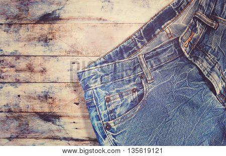 Blue jeans denim on wooden background vintage filter effect