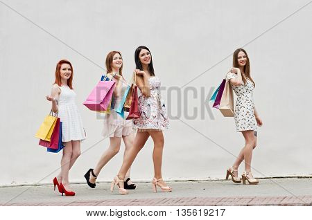 Walking around. group Women walking with Shopping Bags On City Street about wall