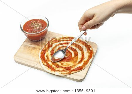 Pasting Pizza Sauce On Pizza Dough [isolated White Background]