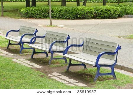 Wooden Benches With Blue Arm Bands In Public Park