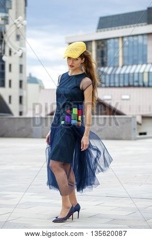 Portrait in full growth, young beautiful brunette woman in a blue dress walking on the street, summer city outdoors