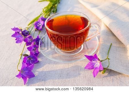 English tea in the garden. Cup of tea served on the linen tablecloth with blue bell flowers in the garden. Rustic tea time concept.