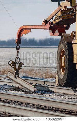 Railway crane machine lifting short piece of rail